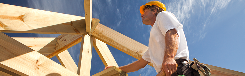 Construction inspector climbing up the staircase of a wooden frame of a home in construction holding.